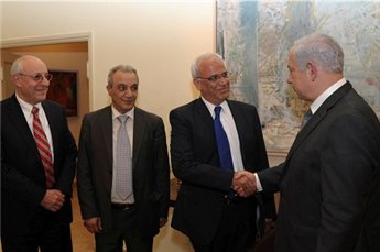 Netanyahu shakes Saeb Erekat's hand during their meeting on 17 April (Maan)