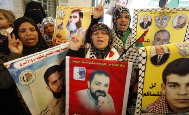 Protestors, carrying signs with pictures of hunger strikers.
